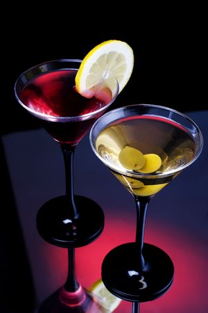 Classical martini in glass on reflection surface, garnished  olive and lemon. Stock Photo - 6450271