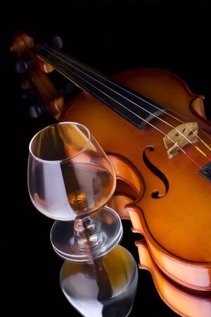 snifter: Snifter glass of cognac and violin Stock Photo