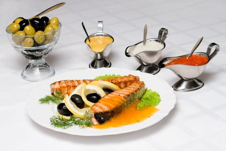 Grilled salmon fish with fresh, served up with different dressings photo