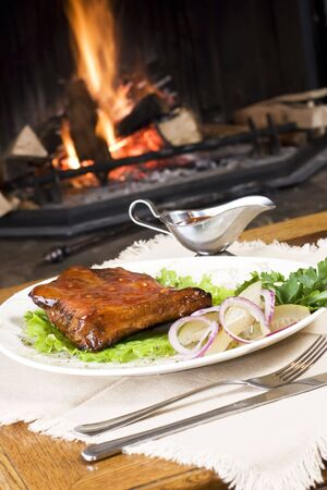 garnishments: Meal of meat with vegetables and garnishments on a white plate, sitting on a table in front of a burning fireplace.
