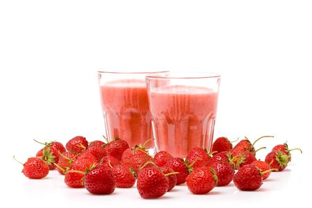 A glass of strawberry smoothie surrounded by fresh berries photo