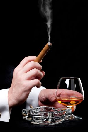 cigar smoking man: Person holding a cigar and drink cognac
