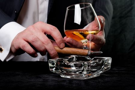 Man smoking cigar and drink cognac