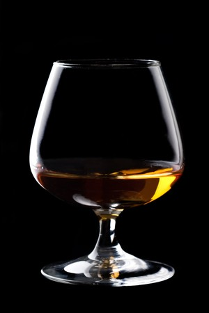 snifter: Snifter glass of cognac on black background.