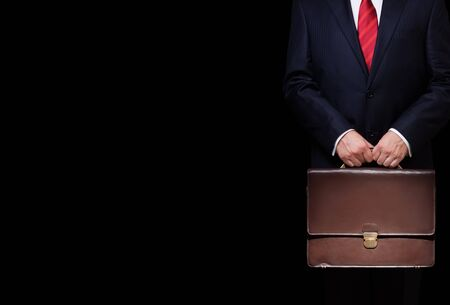 black briefcase: business person holding a briefcase