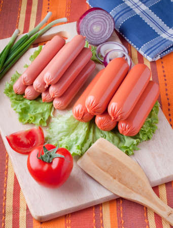 boiled sausage: boiled sausage, on a wooden cutting board.