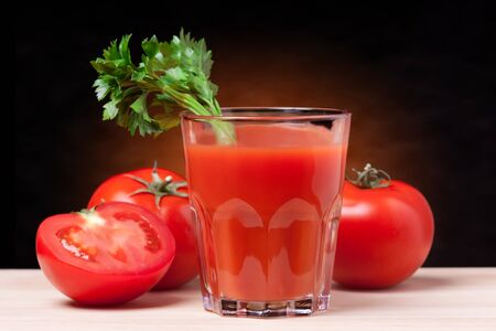 Fresh tomatoes and a glass full of tomato juice.  photo