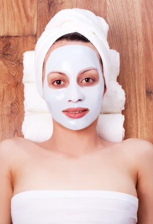 beautiful young woman with cosmetic mask on her face photo