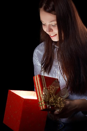 beautifull girl opening gift box. Black background photo