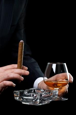 hombre fumando puro: Hombre fumando puros y bebida de co�ac Foto de archivo