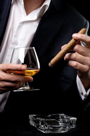 hombre fumando puro: Hombre fumar cigarros y beber co�ac Foto de archivo