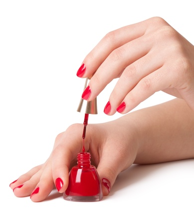 Manicurist applying red nail polish on female fingers photo