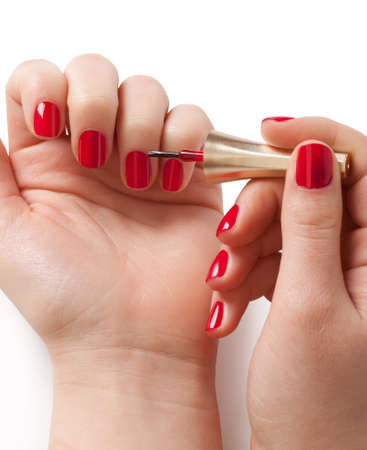 human fingernail: Manicurist applying red nail polish on female fingers