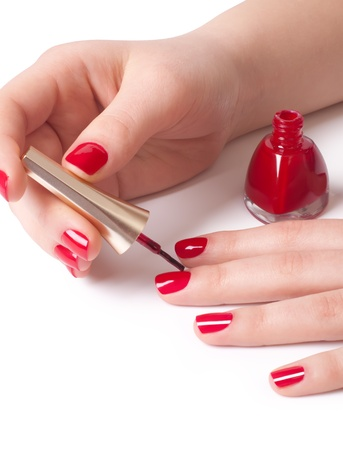 hand painting: Manicurist applying red nail polish on female fingers