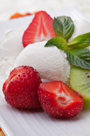 Ice cream dessert with strawberries and kiwi on a white table. photo