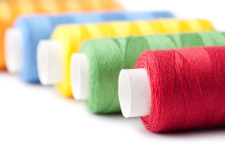 Pile of coloured bobbins of thread isolated on white photo
