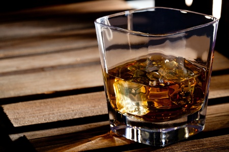 Glass of scotch whiskey and ice on a wooden table Stock Photo