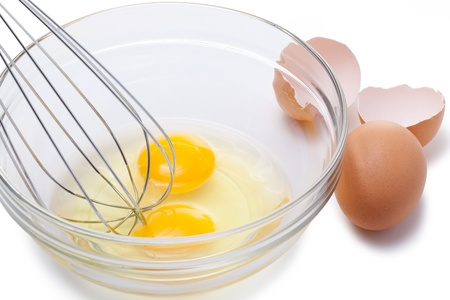 whip: Wire whisk and brown eggs, isolated on white.