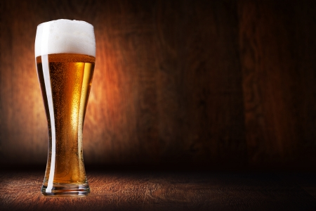 glass of beer: Glass beer on wood background with copyspace
