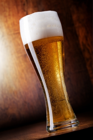 Glass beer on wood background photo