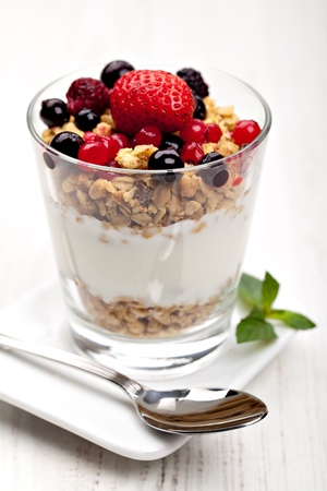 yogurt with muesli and berries in small glass photo