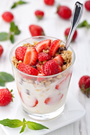 yoghurt with granola and strawberries in glass photo