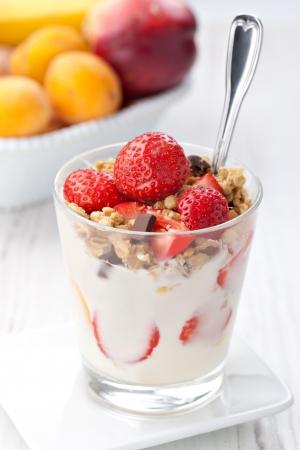 yogur: yogur con granola y las fresas en vidrio