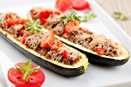 calabacin: Mitades de calabacín rellenas de carne picada y verduras Foto de archivo