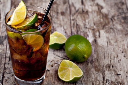 cola: Cuba Libre Drink with lime on a wooden table