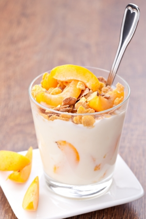 yogurt with muesli and apricot in small glass photo