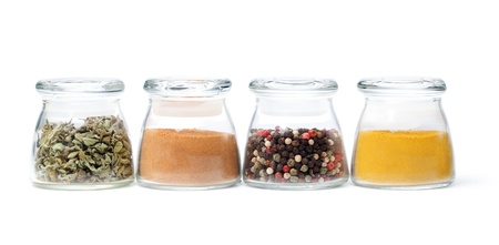 Spices in glass containers on a white background photo