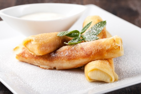 powdered sugar: Rolled pancakes with powdered sugar and mint