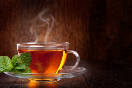 teacup: Cup of tea and mint on a wooden background