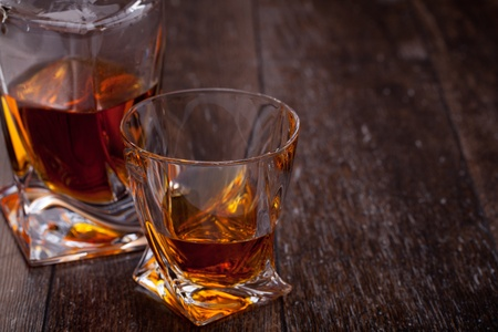 Glass of scotch whiskey on a wooden table photo