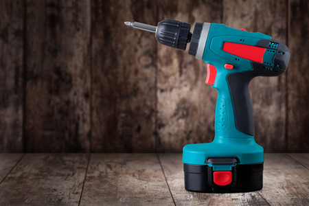 tool chuck: Battery screwdriver on a wooden background Stock Photo
