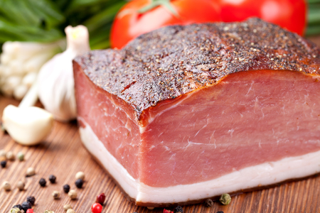 speck: Italian speck on a wooden table Stock Photo