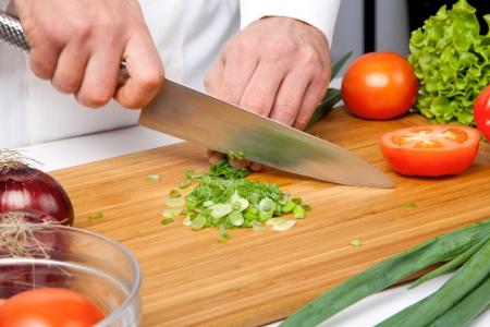 mans hands cutting tomato. Salad preparation photo