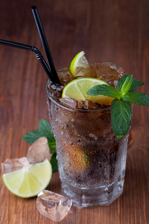 Cuba Libre Drink with lime on a wooden table photo