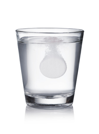 Glass with effervescent tablet in water with bubbles on white  background Standard-Bild