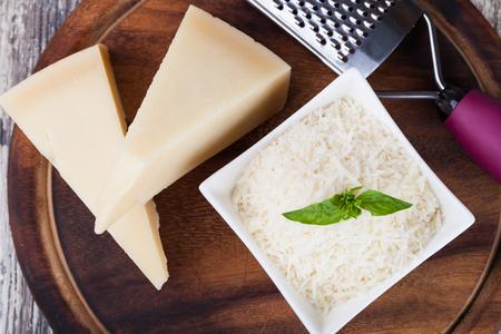 queso rallado: queso parmesano rallado y rallador de metal sobre plancha de madera Foto de archivo
