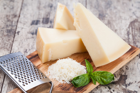 parmesan cheese: grated parmesan cheese and metal grater on wooden board