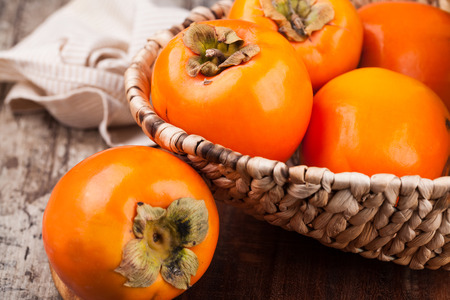 persimmons: persimmons on wooden background