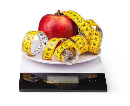 electronic balance: Apple with measuring tape on a digital kitchen scale
