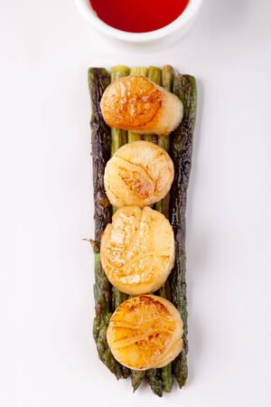 broiled: fried scallops with asparagus on a white plate and sauce