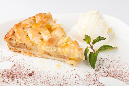 Piece of cake charlotte with apples ice cream and fresh mint on a white plate
