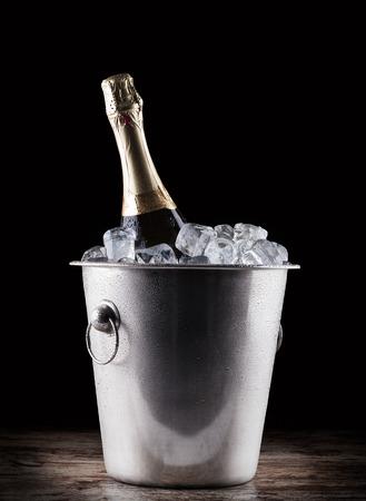 bouteille champagne: bouteille de champagne dans un seau avec de la glace sur le fond sombre
