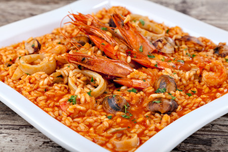 calamar: Paella española, arroz con mariscos en un plato blanco. De cerca