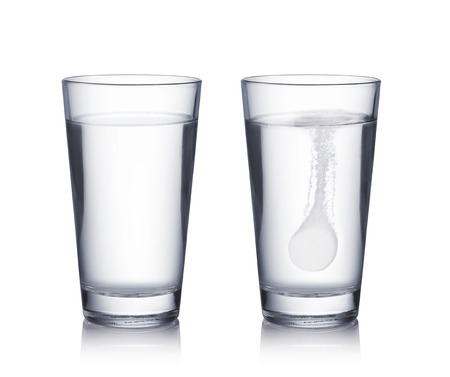 effervescent: Glass with effervescent tablet in water with bubbles on white  background Stock Photo