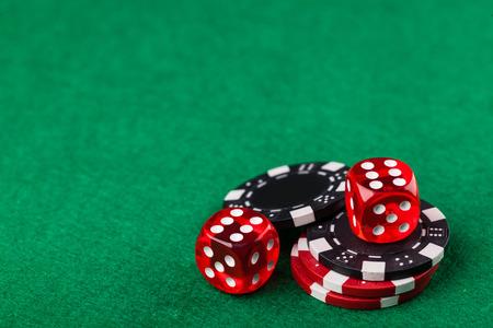 dados: Dados rojos y fichas sobre la mesa verde