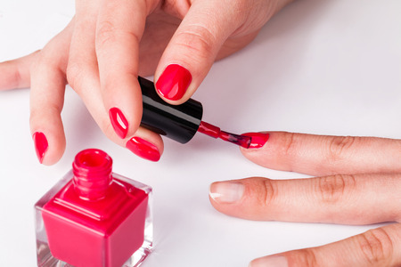 red nail colour: Painting polish on fingers with red nails